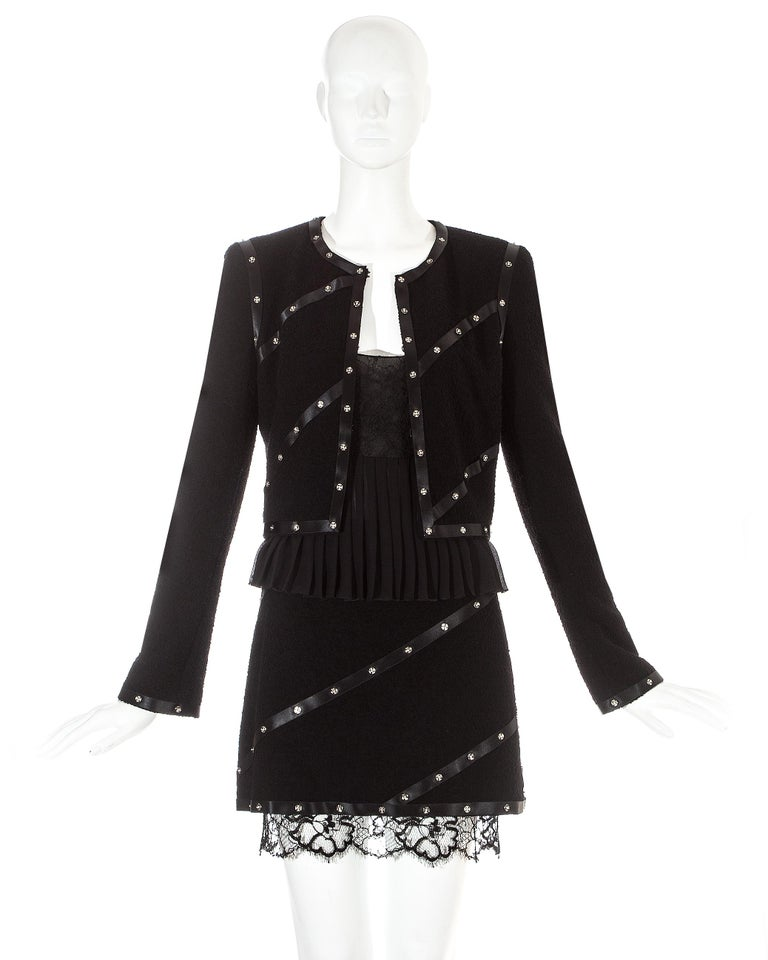 Chanel by Karl Lagerfeld, 3 piece skirt suit. Long sleeve fitted jacket with silk ribbon bands and metal press studs. Matching mini skirt with lace hem. Silk chiffon pleated cropped vest with lace bra.  Fall-Winter 2003