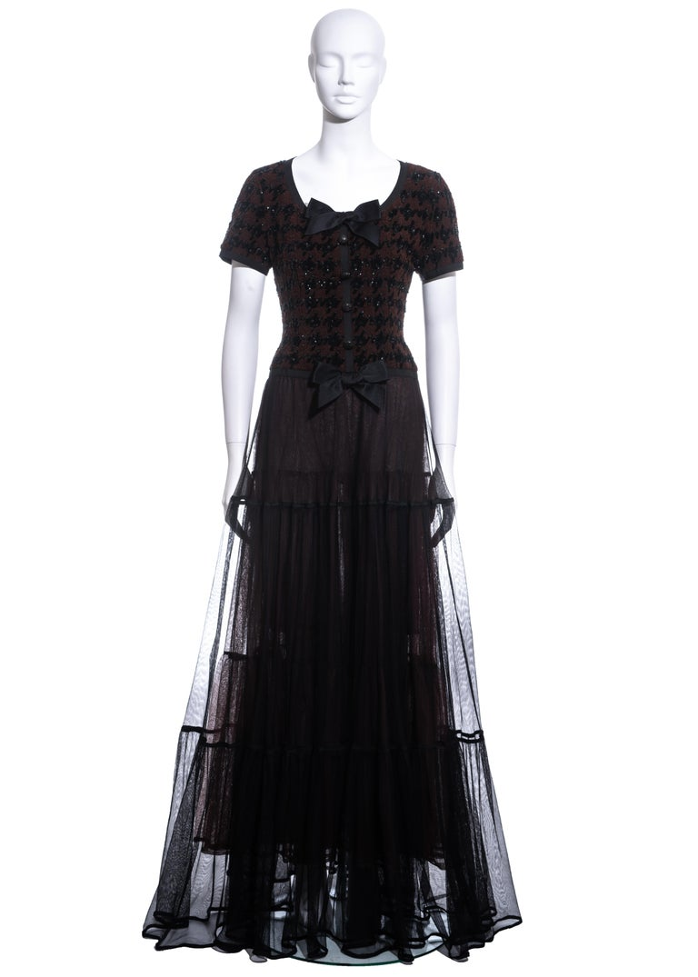 ▪ Chanel brown and black houndstooth maxi dress ▪ Designed by Karl Lagerfeld ▪ Sequin houndstooth pattern ▪ Two silk bows  ▪ Maxi skirt made up of four layers of silk tulle with ribbon trim  ▪ Beaded buttons  ▪ Zip fastening at back  ▪ Bust 34