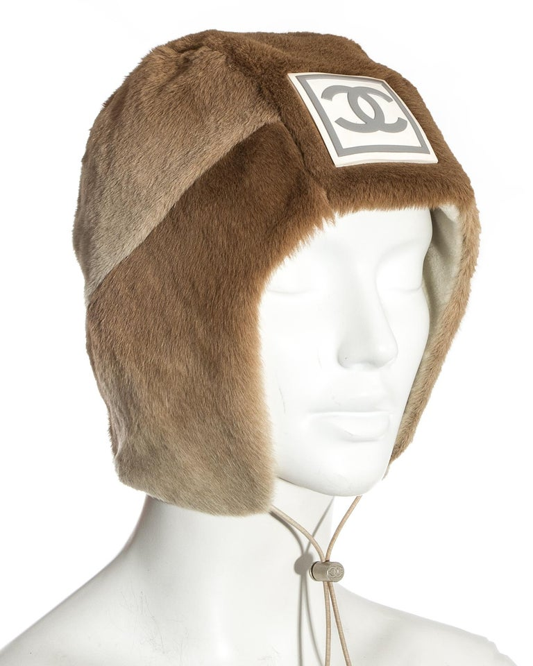 Chanel by Karl Lagerfeld; fawn sheared fur trapper hat. Large rubber interlocking C logo at the front, silver toggle drawstring fastening, cream fleece lining.  Fall-Winter 2001