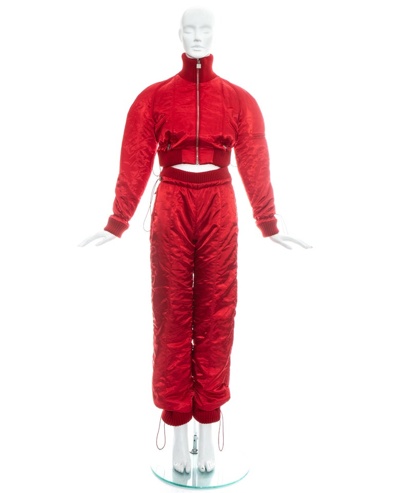 Chanel by Karl Lagerfeld; red polyester tracksuit with ribbed wool. Cropped bomber jacket with turtleneck, zip fastening, two front pockets, one pocket on the sleeve and adjustable drawstring toggles on waistband and wrists. High waisted track pants