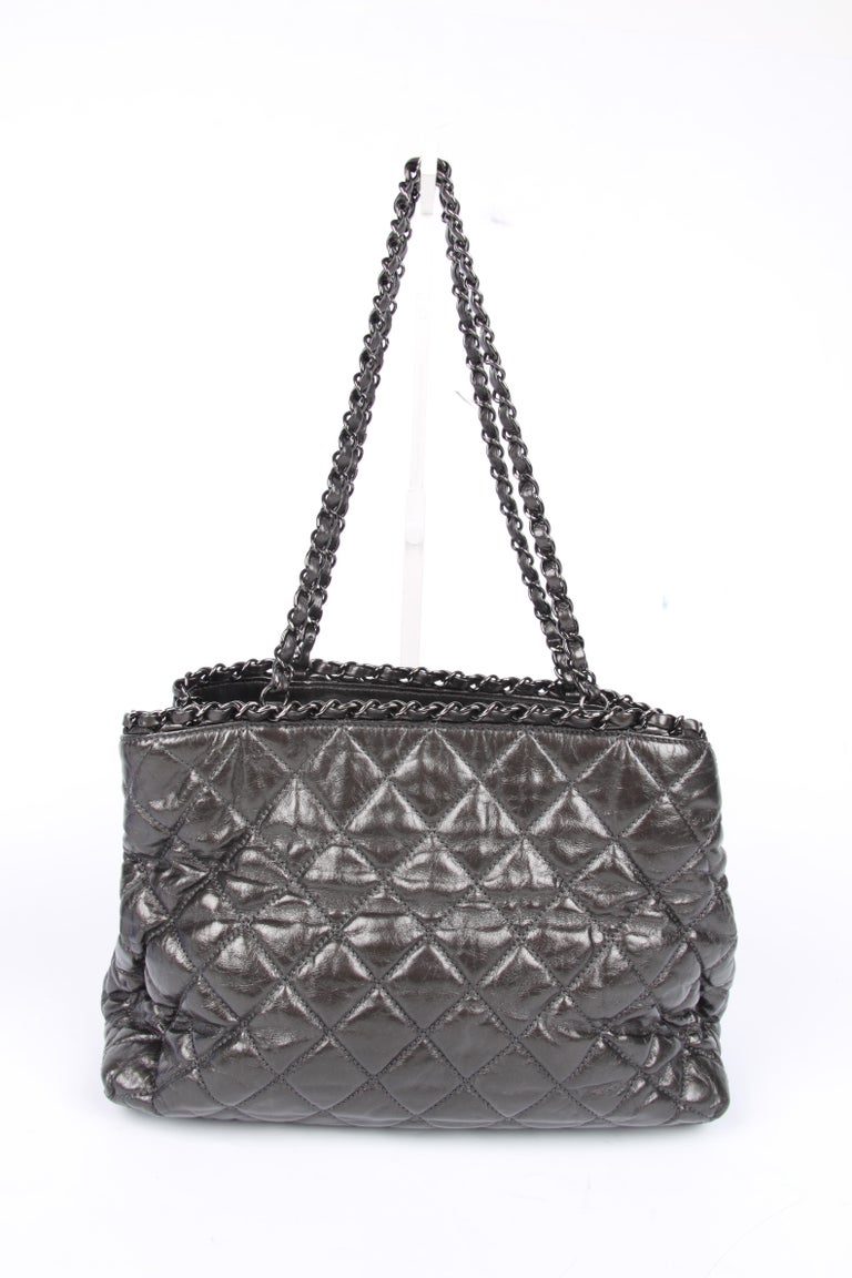 Wowww! Another adorable bag by Chanel; this is the Chain Me Tote Bag.  Crafted from calf-skin leather with a grey metallic finish. A large stitched frontal Chanel CC logo at the front and blackish/silver hardware. The shoulder chains each measure 59