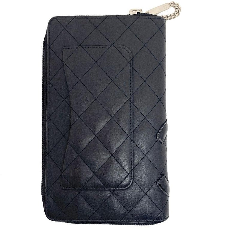 Chanel 'Cambon' wallet in matte black quilted leather with a CC varnished. The interior is in pink fuchsia monogram leather. Zip closure. Silver metal hardware. It is composed of: 16 card slots, 4 billfolds and a coin purse. It comes from private