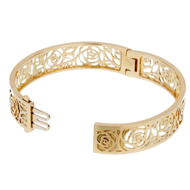 The camellia, Gabrielle Chanel's favorite flower, is the inspiration for this exquisite bangle from the Chanel Camellia collection. A polished 18k yellow gold flower motif flows through the entire length of the bangle.  Width: 1/2