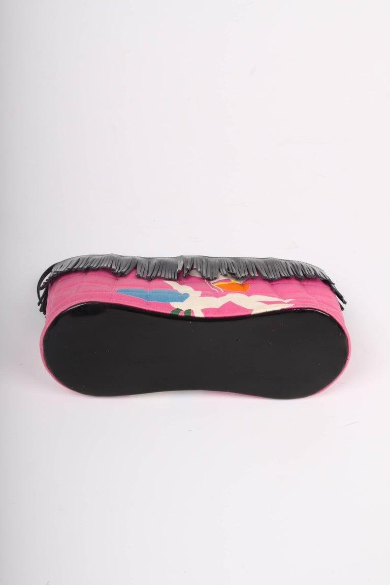 Sweet little bag by Chanel crafted from pink canvas and black patent leather.  The canvas is quilted and embellished with a print in white, orange, yellow, blue and green. The handles, fringes and bottom are made of shiny black patent leather.