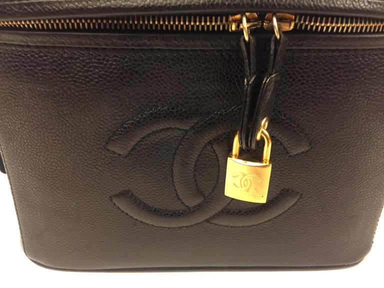 """- Vintage 90s Chanel black caviar vanity bag. """"CC"""" logo in front.   - Zip closure and gold lock with key.   - Interior with compartments.   - Measurements: 24cm x 17cm x 16cm. Drop handle: 3cm."""