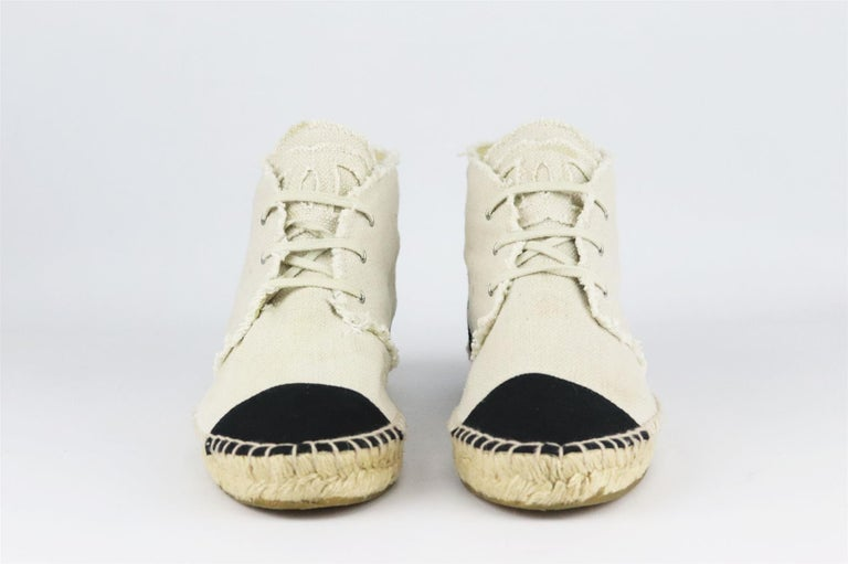 Chanel's lace-up espadrilles in cream linen, featuring the brand's trademark interlocking CC logo on the tongue in a matching frayed cream linen, they have a thick jute sole and a reinforced canvas toe which offers a comfortable and supportive fit.