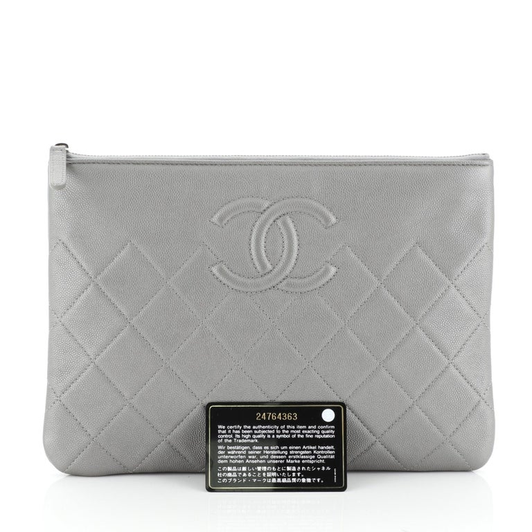 This Chanel CC O Case Clutch Quilted Caviar Medium, crafted from gray quilted caviar leather, features silver-tone hardware. Its zip closure opens to a gray nylon interior. Hologram sticker reads: 24764363.   Estimated Retail Price: