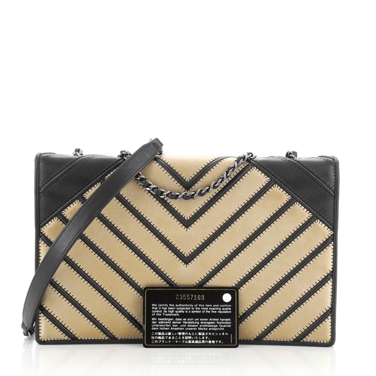 This Chanel Chevron Couture Flap Bag Stitched Chevron Lambskin Medium, crafted in black and gold leather, features woven-in leather chain strap with leather pad, black fabric side panels and gunmetal-tone hardware. Its turn-lock closure opens to a