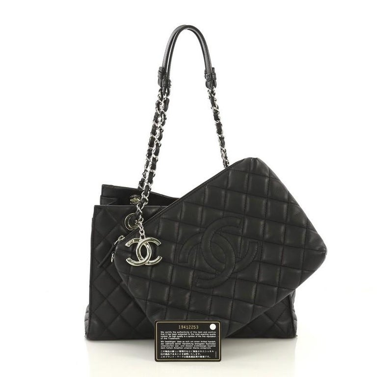 This Chanel Chic and Soft Shopping Tote Quilted Calfskin Small, crafted in black quilted calfskin leather, features woven-in leather chain straps with leather shoulder pads, CC charm, and silver-tone hardware. Its wide top opening showcases a black