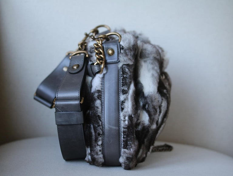 This super-chic shoulder and cross body bag is crafted in plush fur and leather accents. The bag features a bronze chain drawstring feature threaded through the opening of the bag. Chanel CC clasp push lock tightens the chain fastening. Grey leather