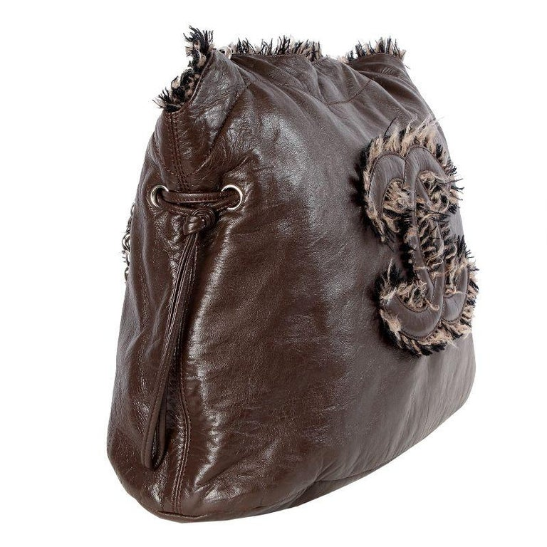 Chanel shoulder bag in brown soft leather. CC logo on the front is highlighted with wool fringes. Silver chain is ranged in leather and wool fringes. Opens with a magnetic button and the hem is framed in wool fringes. Lined in gray satin with one