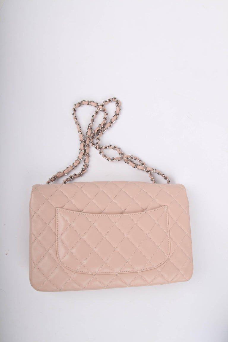 This highly sought after bag is called Chanel 3 Flap Bag. We love it.  The name says it al; it has three compartments, immediately visible on the exterior. The bag is crafted from soft lambskin leather in very light shade of pink. Silver-tone