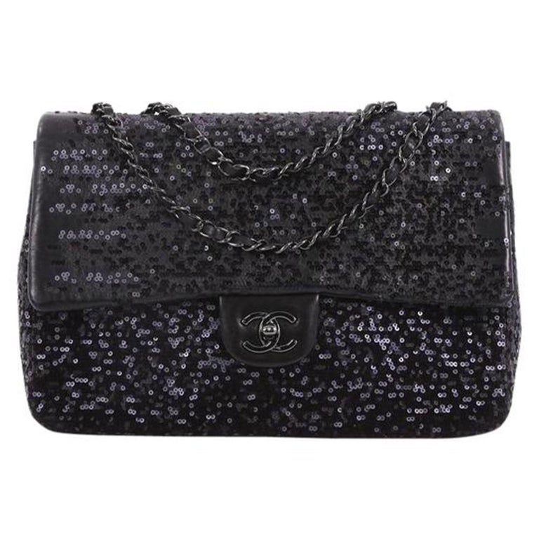 This Chanel Classic Single Flap Bag Sequins Jumbo, crafted in black sequins, features woven in leather chain link strap, exterior back slip pocket, and gunmetal-tone hardware. Its CC turn-lock closure opens to a black fabric interior with zip