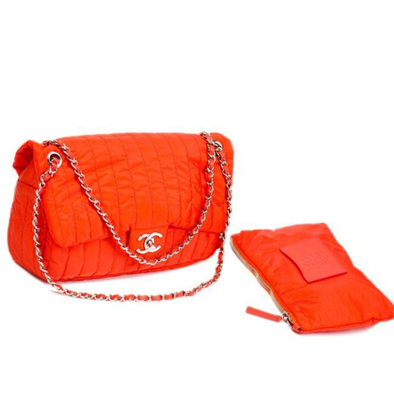 Chanel Soft Shell Flap Bag Vertical Quilted Nylon Jumbo is a limited edition piece from the brands' Spring 2012 Collection. Crafted from red orange quilted nylon, this chic bag features woven-in leather chain strap, front flap with CC turn-lock