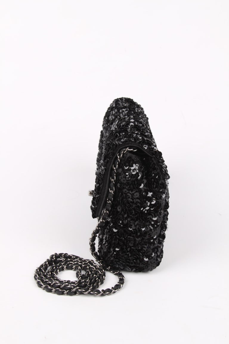 Adorable! A Chanel bag in black leather covered with sequins.  Magnificent bag, the leather is fully covered with black shiny sequins. A silver-tone turnlock CC closure at the front and a silver-tone chain that measures 114 centimeters and is
