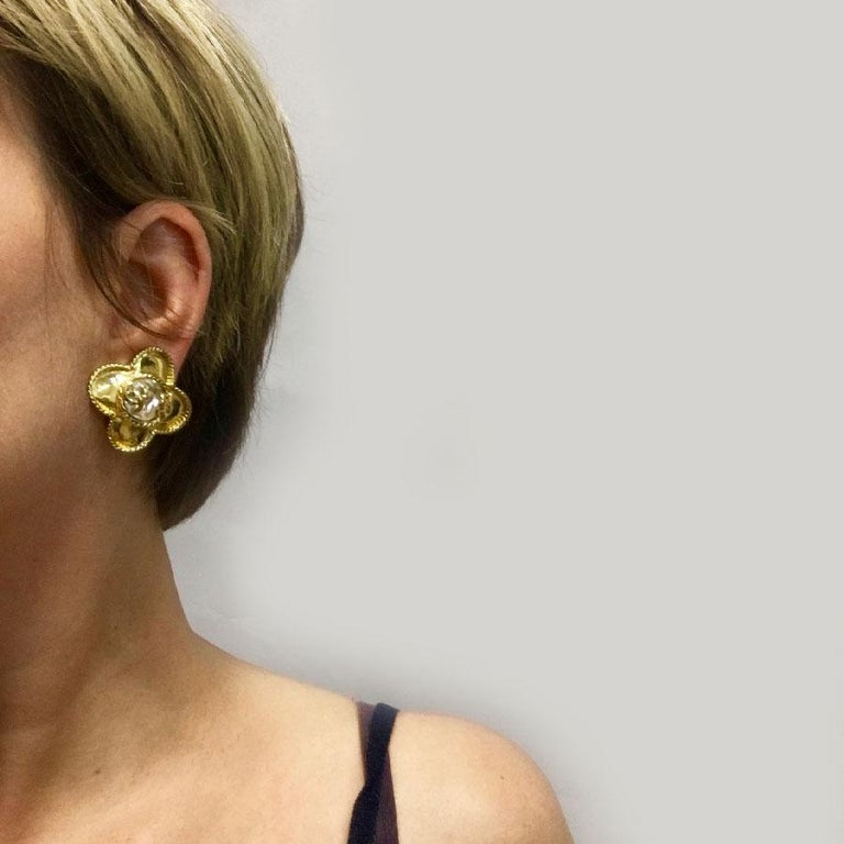 Rare vintage Chanel clip-on earrings with the iconic clover and CC. Made of gilded metal with fine gold and large rhinestones in the center. In very good condition. (signs of wear on the back of the jewel). Comes from the Fall / Winter 1995's