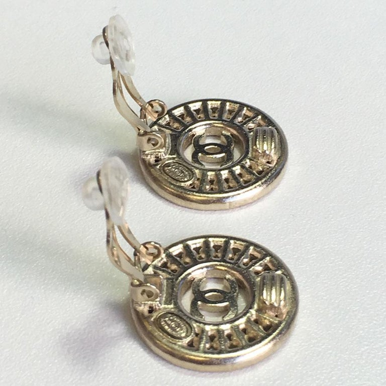 Elegant pair of round earrings CHANEL clips. In matte gold metal, set with emerald cut rhinestones, pearly pearls and a hammered CC in the center. Never worn. Brand stamp on the back. Collection 2015. Dimensions: 2.3 cm in diameter Delivered in a