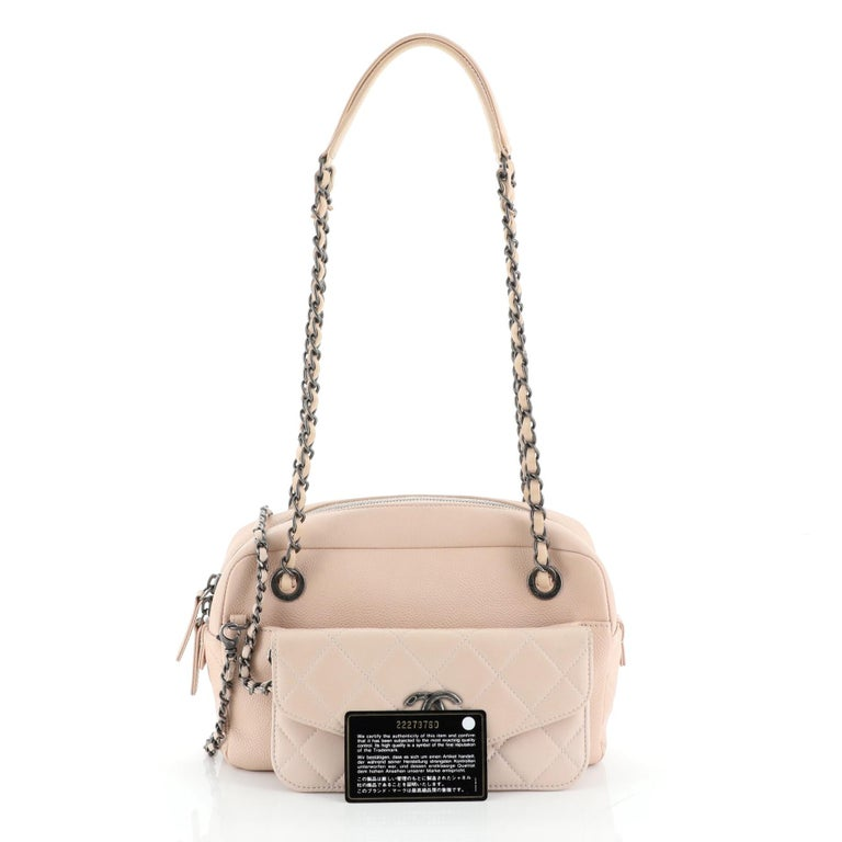 This Chanel Coco Break Camera Case Caviar Medium, crafted in pink caviar leather, features dual woven in leather chain link straps with leather pads, front quilted lambskin insert with CC logo, and aged silver-tone hardware. Its zip closure opens to