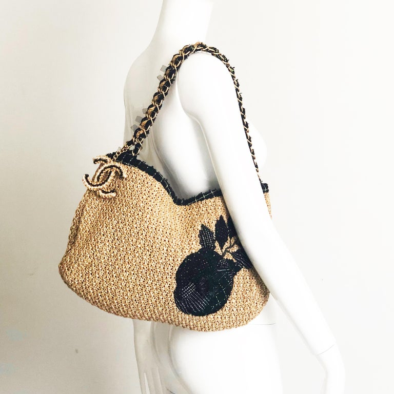 Authentic, preowned Chanel Coco Country Camellia Woven Straw shoulder bag, circa 2010. Woven straw trimmed in boucle wool w/gold metal hardware & attached CC logo charm. Lined in fabric w/1 zip pocket, 1 open split pocket. Fastens w/magnetic
