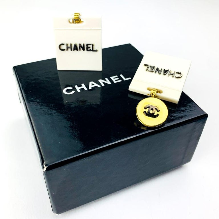The clips are from Maison Chanel. They each represent a beige bag with the inscription CHANEL. The clasps are made of gilded metal and include the CC emblem of the brand. For a perfect fashion and trend look. The clips are vintage (80s) and in good