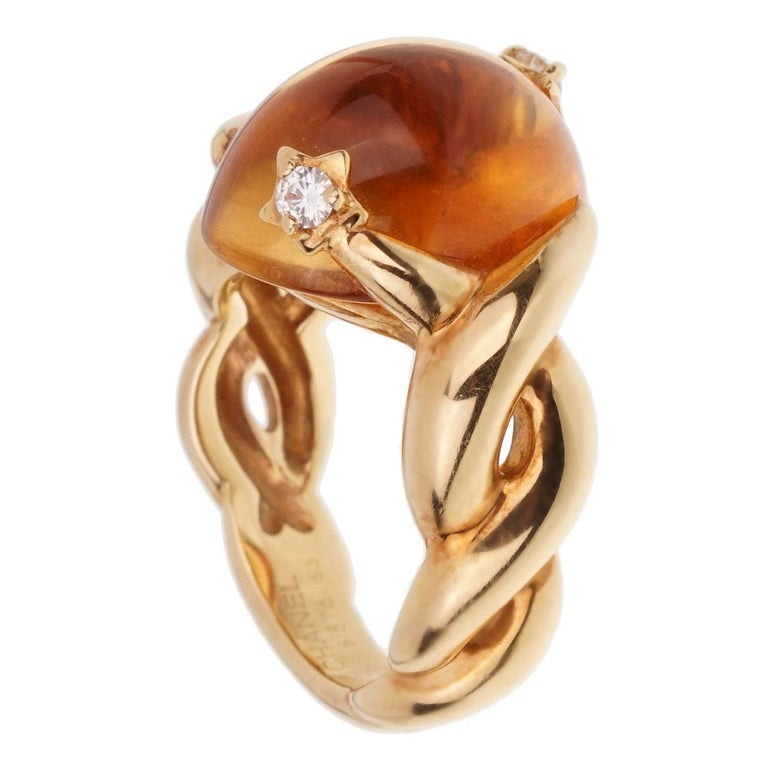 A fabulous authentic Chanel yellow gold cocktail ring showcasing a cabochon Citrine adorned with 2 round brilliant cut diamonds in 18k gold.  Size 6 1/4 (Resizeable)