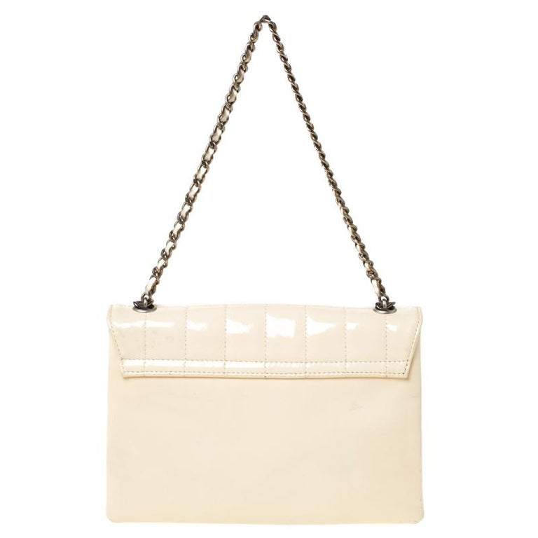 Wear it with your formal looks or dressy evening looks, this beautiful Chanel flap bag is elegant and chic with a timeless look. Crafted in cream patent leather, this bag features chocolate bar-like quilting all over the exterior along with black