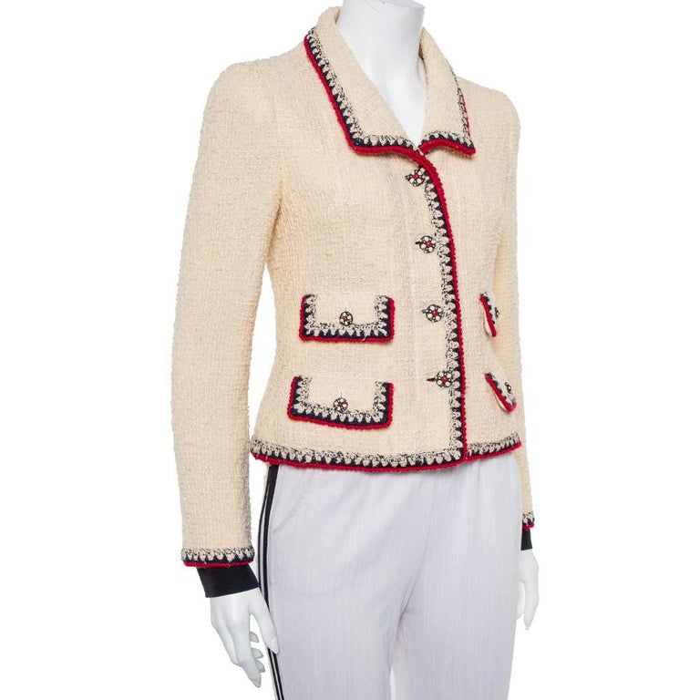 The use of tweed to craft exquisite creations that never go out of style is a signature of Chanel. This classic buttoned jacket is a piece of fashion history that will never disappoint. Crafted from cream tweed, it has a button front and a