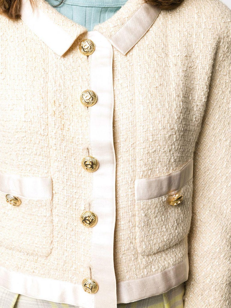 Meticulously crafted in France from a contrasting two-tone palette of cream and ivory tweed, this sophisticated pre-loved skirt suit by Chanel gives a modern update to the brand's signature knit. The jacket features a classic collar, a