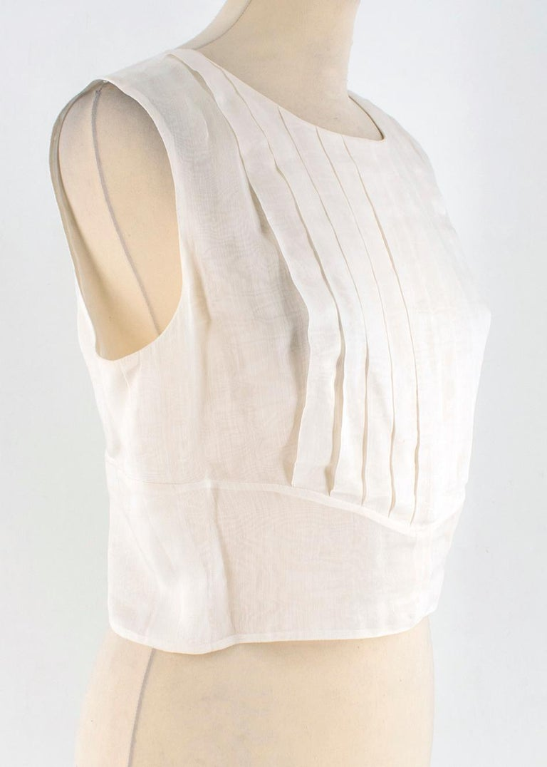 Chanel Cropped White Pleated Silk Top  -Silk Blend, white colour -Sleeveless  -Cropped cut -Pleated front  -Open-back  -Hook and fasten closure on back -Stripped white buttons with signature
