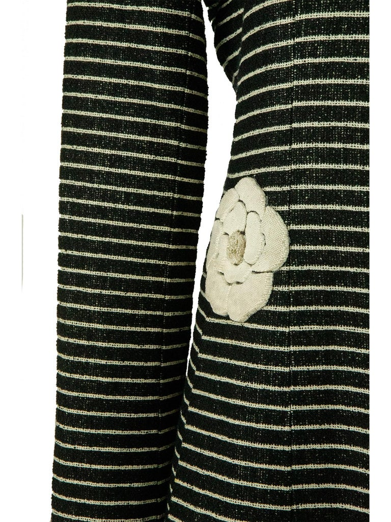 From the 2001 Chanel Cruise collection, comes this horizontally striped white on the black long coat. The coat has a fitted bodice grown into a flared skirt and features a short notched lapel collar. The waistline features a textured camellia, the