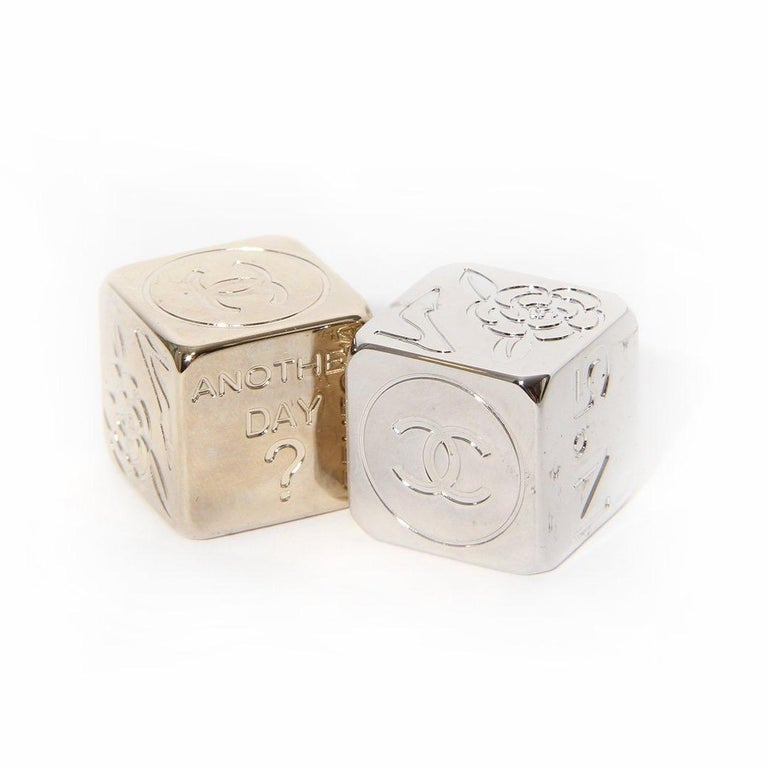 Dice by Chanel  One gold-tone die  One silver-tone die Six different engraved designs  1. CC logo  2. Camellia flower and heel  3. Quilted handbag  4.