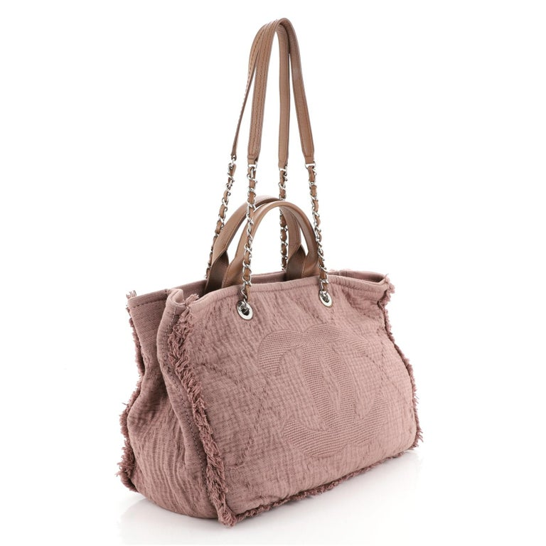 This Chanel Double Face Deauville Tote Fringe Quilted Canvas Medium, crafted in pink quilted canvas, features dual woven-in leather chain straps, dual top handles, CC logo at the front, and silver-tone hardware. Its magnetic snap closure opens to a