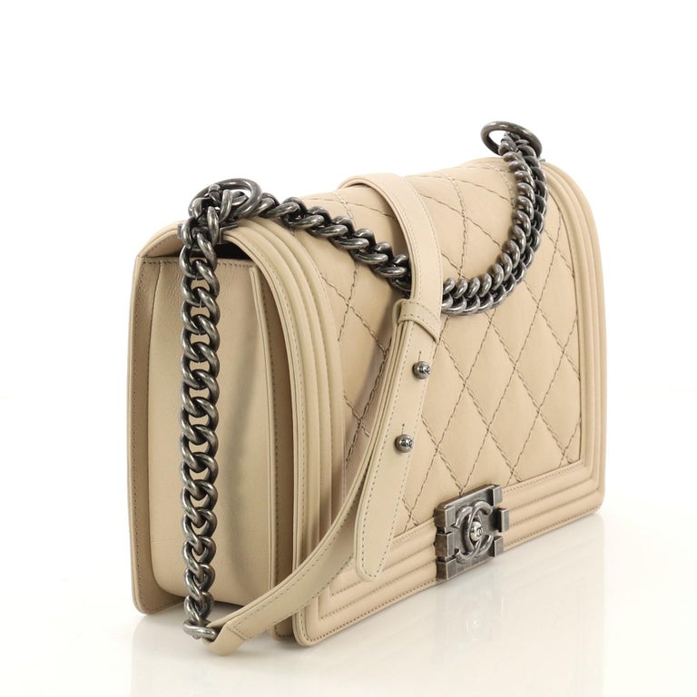 This Chanel Double Stitch Boy Flap Bag Quilted Calfskin Old Medium, crafted from beige quilted calfskin leather, features chain link strap with adjustable leather pad and aged silver-tone hardware. Its CC boy push-lock closure opens to a grey fabric
