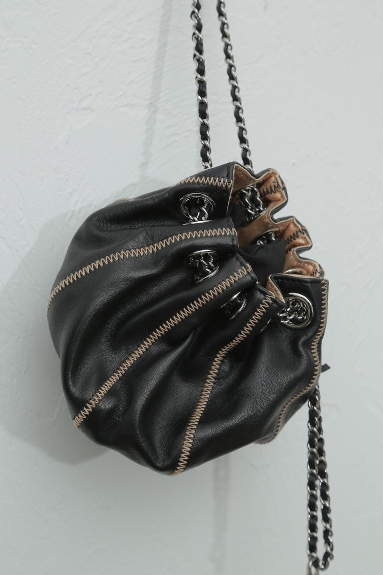 Like new This item may have been worn but has no visible signs of wear.  Description: This stylish pouch is rafted of luxuriously soft lambskin leather in black. This bag is stitched in a sac form with light pink stitching. The bag features silver