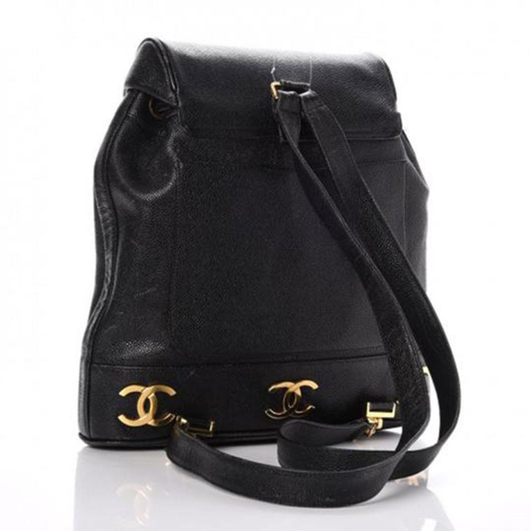 Chanel Vintage Caviar 1990s CC Drawstring Rucksack   The backpack features gold Chanel CC logos along the bottom trim, gold hardware and two lengthy leather shoulder straps. The flap opens to a matte black leather interior with companion pouch. This