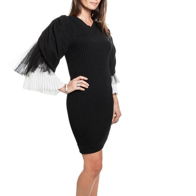 Chanel lovely black cotton dress. Size 36 FR. Excellent condition. Spring 2009 Collection  It is in stretch fabric and has a characteristic, its sleeves!  There are 3 overlays in white, and black veil. V-shaped.  flat dimensions: shoulders 36 cm,