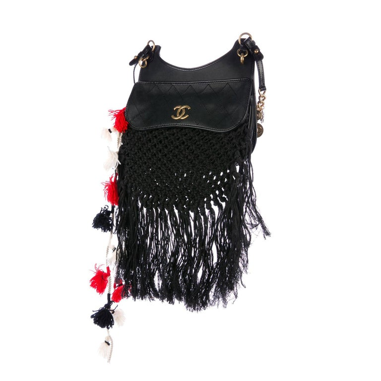 Chanel Dubai Resort Runway Limited Edition Fringe Crochet Pom Pom Bag  2015 Dubai Cruise Collection  Iridescent black calfskin Antique gold hardware Medallion embellished chain strap  Pom poms in red white and black  Magnetic closure Interior black