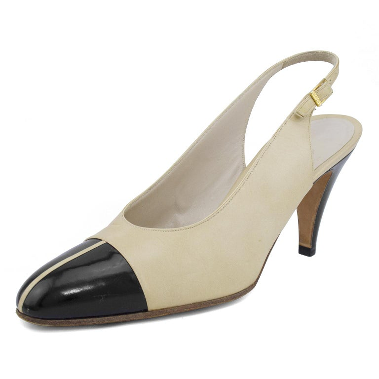 Early 1990s Chanel slingbacks. Beige leather with contrasting black leather cap toe. Slightly mod inspired with a vertical beige line down the centre of the black cap toe. Cream leather interior with metallic gold brand stamp. Gold-tone branded