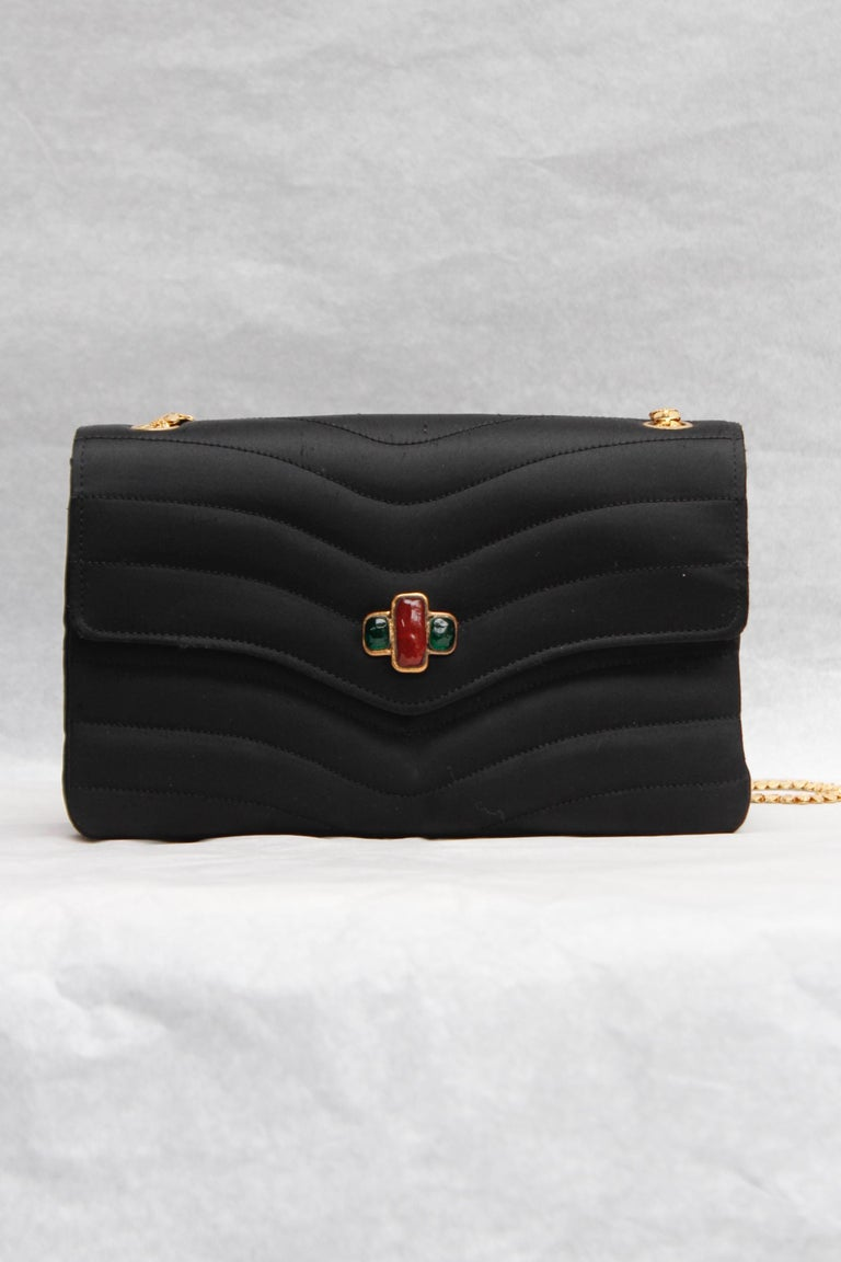 CHANEL (Made in France) Elegant evening bag in black satin over stitched with waves pattern. The flap is decorated with a a gilded metal and ruby and emerald glass paste element. It can be worn over the shoulder or cross-body, thanks to a lovely
