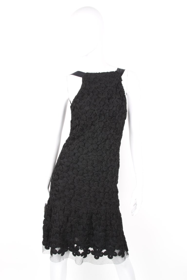 Chanel Fall/Winter 2005 Black Floral Crotchet Camelia Wool Mesh Dress.  Black wool dress accented with mesh paneling from Chanel: sheer fabric with camelia detail thoughout. Back zip and silk shouder details. Main fabric is wool and lined with
