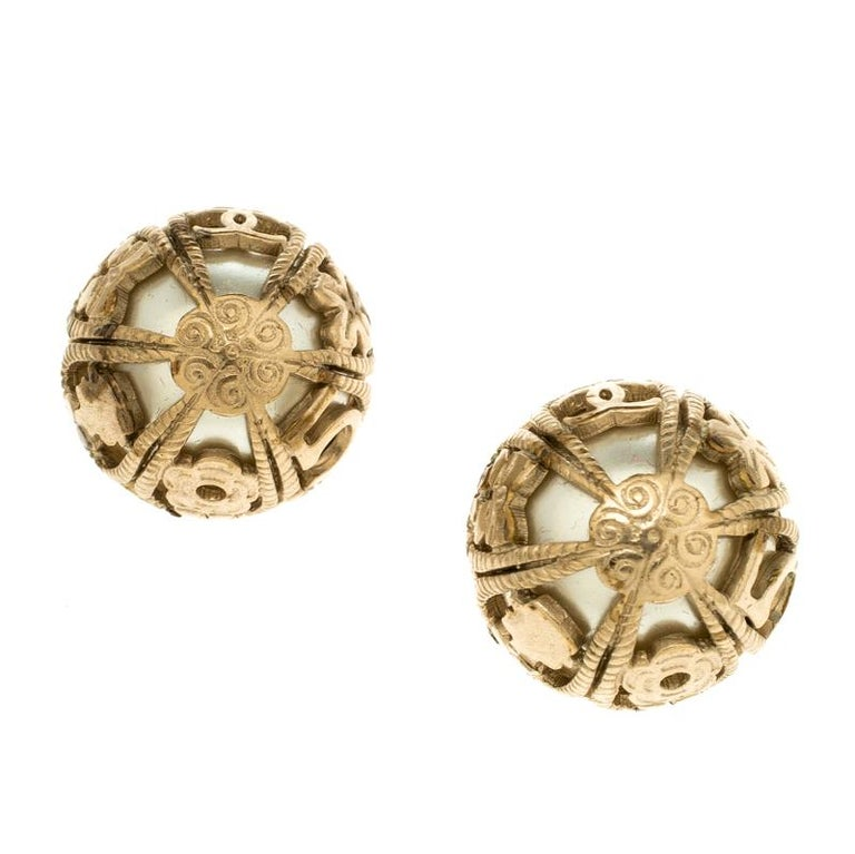 Chanel's dome stud earrings are graceful and sophisticated. The dome shaped carving is molded over a pearl base. The gold-tone earrings come with a stud back closure and are hassle free style making it easy to wear it for long hours or even as an