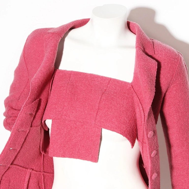Chanel by Karl Lagerfeld  Chanel Fall / Winter 1999 Ready to Wear Collection Made in France  Pink wool felt  Notched collar Single breasted blazer  Four fabric covered buttons  Seam details Fitted waist Detachable fabric panel in front bust of