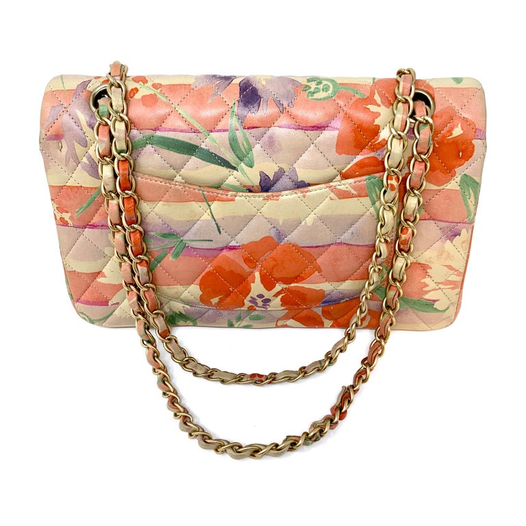 This authentic Chanel Floral Watercolor Double Flap Bag is in excellent condition.  Signature Chanel quilted leather design in serene multicolor floral.  Shades of orange, purple, green and blue flow together on a soft yellow- gold background.