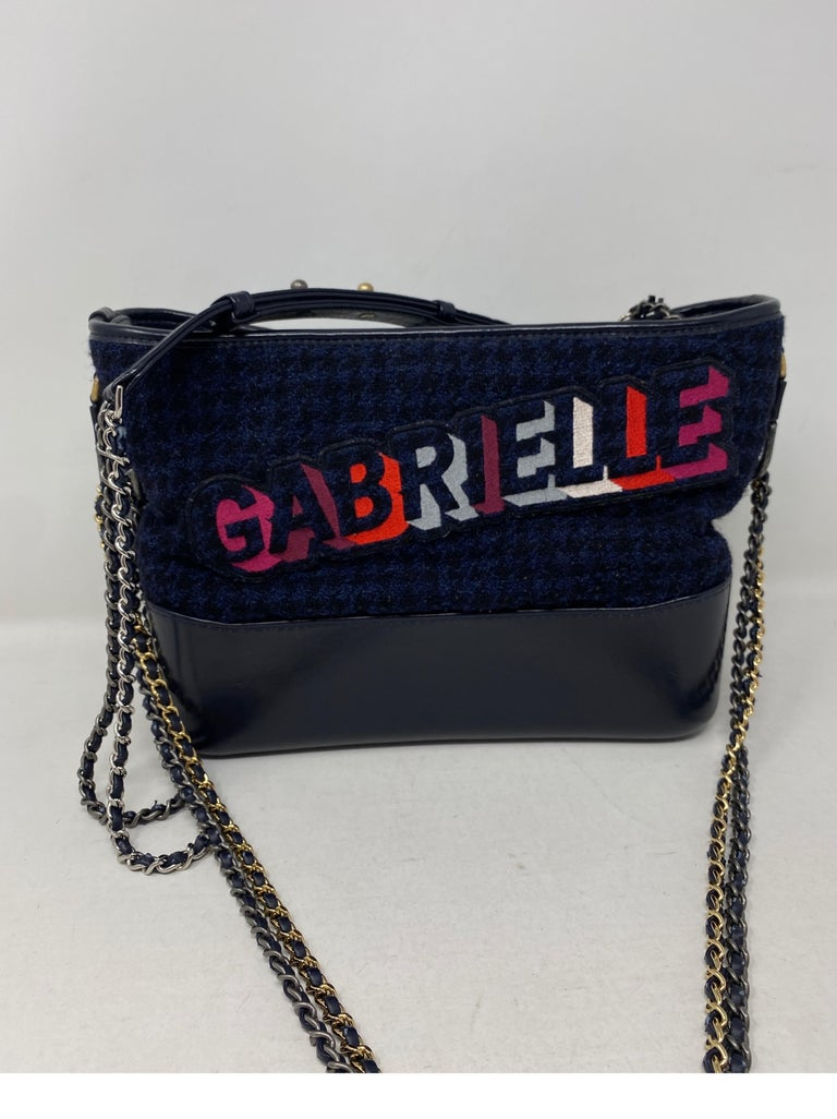 Chanel Gabrielle Crossbody Bag. Gabrielle letters over navy tweed fabric. Leather trim and two tone chains. Mint like new condition. Rare and limited bag. Unique collector's piece. Don't miss out on this one. Guaranteed authentic.