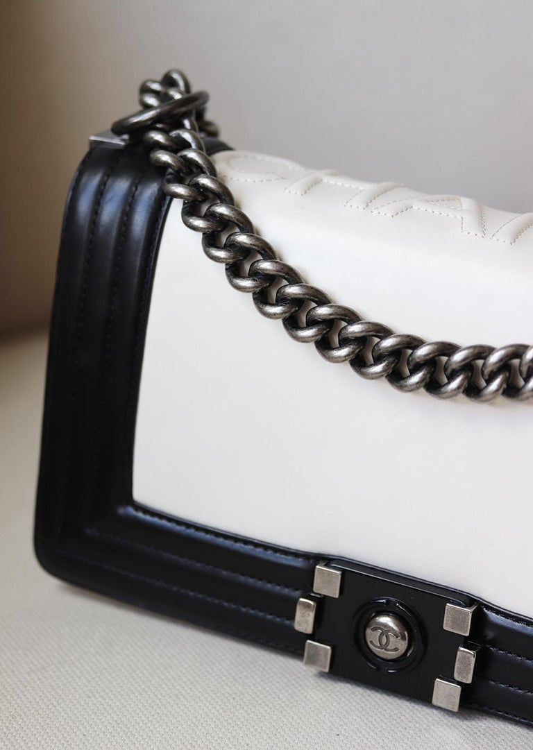 Chanel Glazed Calfskin Leather Boy Flap Bag has been hand-finished by skilled artisans in the label's workshop. Boasting smooth black and ivory calfskin-leather exterior, this design is accented with silver-toned and black calfskin-leather chain