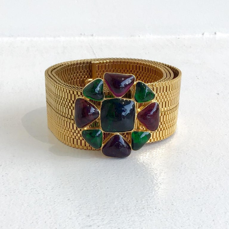 Chanel Gold Belt with Gripoix Glass Embellishments. Features a gold tone lattice belt with a circle buckle containing emerald and violet gripoix detailing.