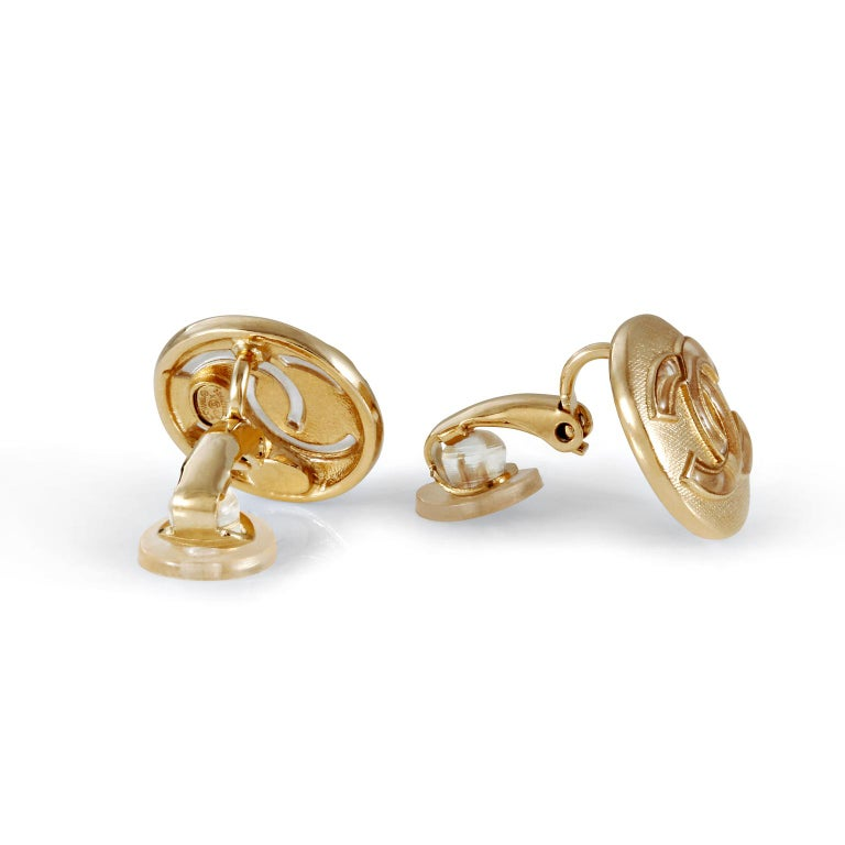 These authentic Chanel Gold CC Mini Button Earrings are in excellent vintage condition.  Very small round earrings, approximately 0.5 inches, in gold tone metal with textured background.  An interlocking CC is centered on each.  Clip on style. Made