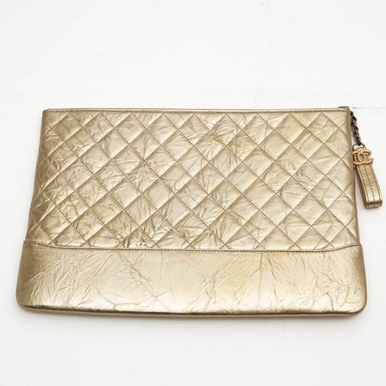 CHANEL clutch in gold aged calfskin. The small chain is made of aged silver metal, zipper with a charm at the end