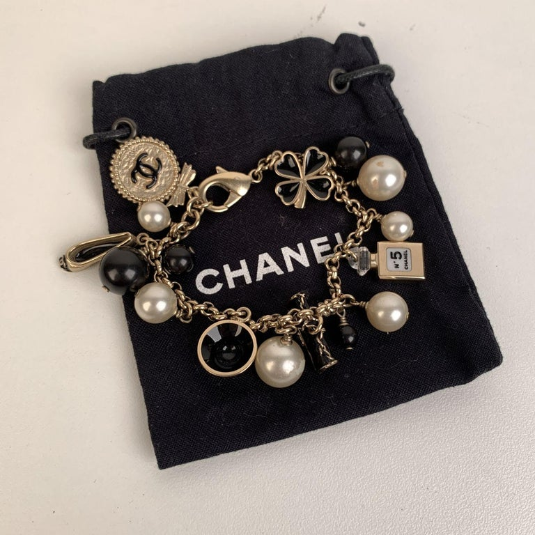 Lovely charms bracelet by CHANEL. Gold metal chain, faux pearls, black beads and iconic Chanel charms (a logo medallion, a bag, a hat, a ballet flat, a clover and a bottle of perfume). Lobster closure. Stamped 'CHANEL - B12 CC A - MADE IN ITALY'