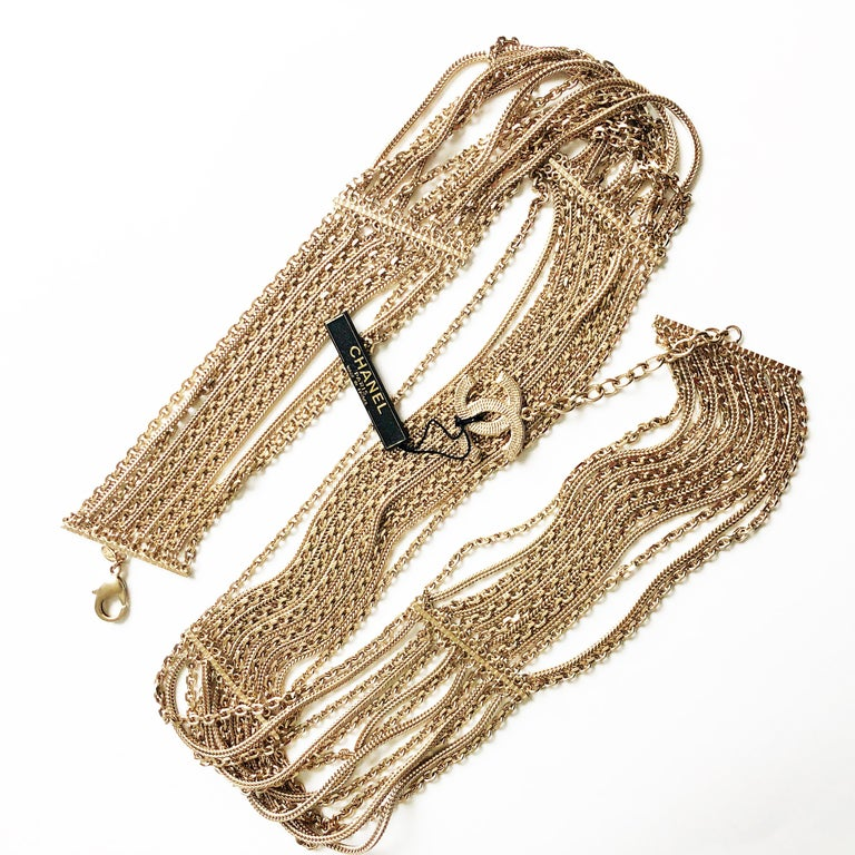 Authentic, NWT/NOS Chanel Multi-Chain Belt with CC Charm, from the 07P collection. Made from gold metal, one can wear this w/the clasp & CC logo charm facing front, back or wear the piece as an over-the-top necklace. It measures 34in L x 2in H with